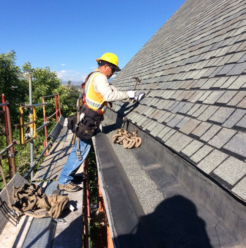 roofer with yellow hardhat working on roof
